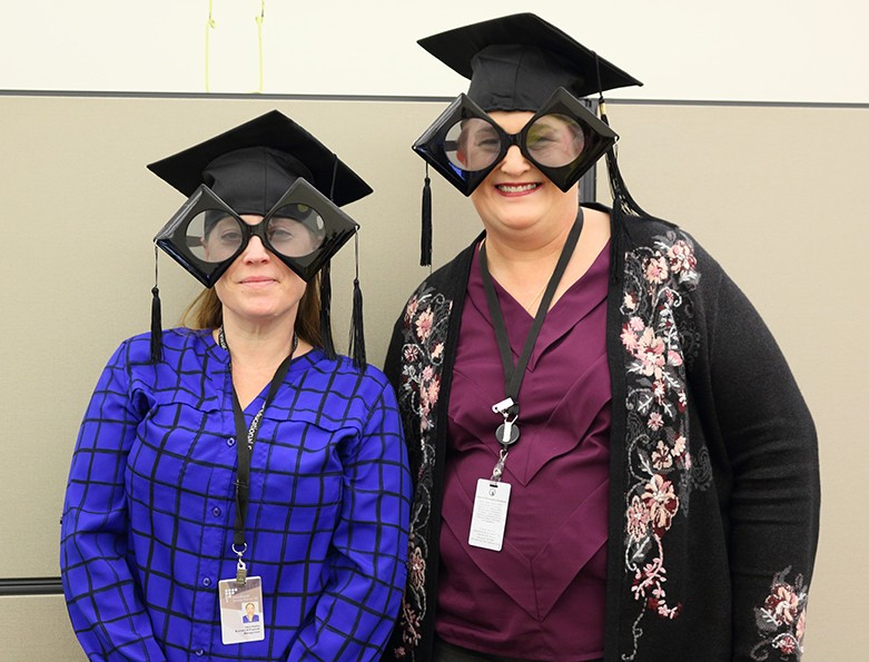 Dana Haxby & Kyla Dordan wearing giant silly glasses and graduation caps